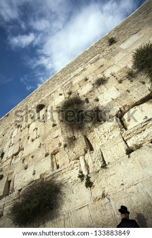 An orthodox Jewish man pressed in prayer against the wailing wall in the old city of Jerusalem. - stock photo