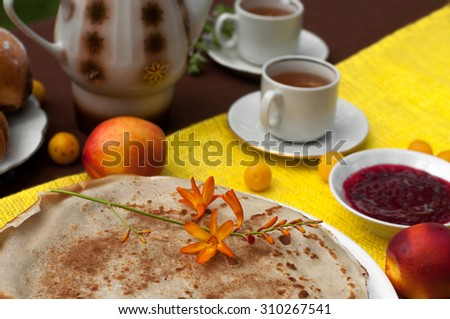 An outdoor composition with tea cups, a tea pot, a plate of pancakes, pastry, ripe fruit and field flowers on a bright yellow and brown table cloth