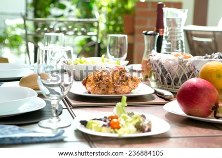 An outdoor dining meal complete with roast chicken, salad, bread rolls, wine and fruit in summer. Concept of outdoor dining.