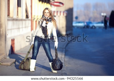 An outdoor portrait of a beautiful long-haired blond young woman on street wearing a white jacket, scarf, skinny jeans and white boots. Taken in on a cold winter day, with shallow depth of field.