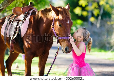 An outdoor portrait of an adorable little girl wearing pink fairy dress giving a kiss to a brown horse in a garden on a sunny summer day - stock photo