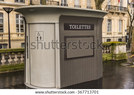 An outdoor public washroom located on a boulevard in Paris France. - stock photo