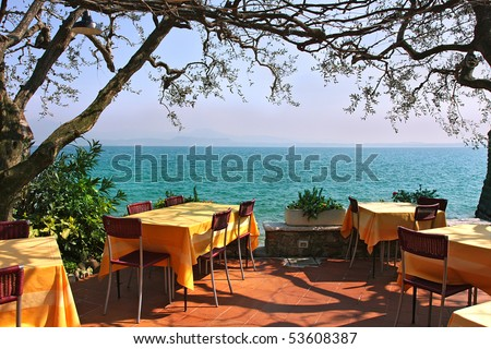 An outdoor restaurant with beautiful view on Lake Garda in Sirmione, Italy. - stock photo