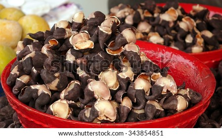 An outdoor vendor sells Chinese water chestnuts in red basins  - stock photo