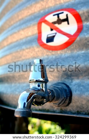 An outdoor water tank tap with water forbidden to drink sign over it. - stock photo