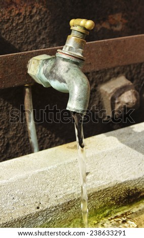 an outside dripping tape wasting precious water  - stock photo