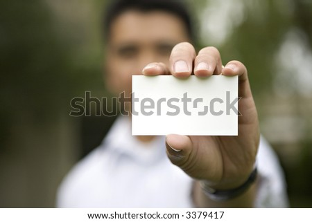An outside shot of a Businessman holding out a Blank Business Card - stock photo