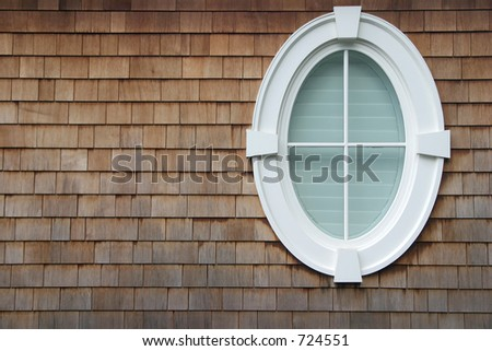 An oval window on the side of a house with shingles.