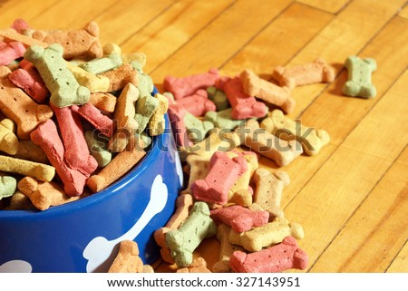 An over abundant supply of various dog treats flowing from a dish. - stock photo