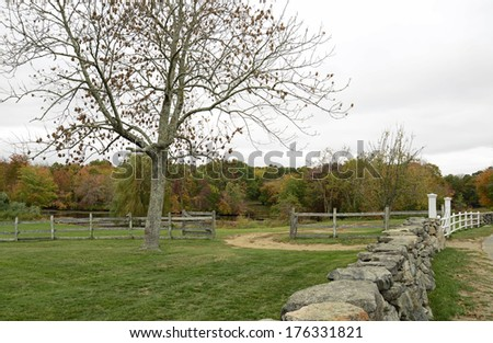 an overcast sky of the Connecticut countryside.  There is a wooden fence and a rock or stone wall with a white wooden gate.  In the background are many trees with colorful leaves - stock photo