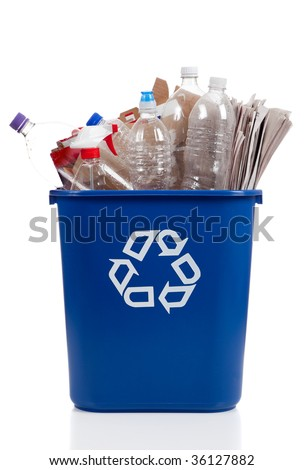 An overflowing blue recycle bin full of  plastic bottles, newspapers and boxes, with the recyle symbol on front - stock photo