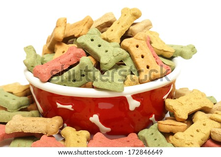 An overflowing bowl full of dog treats. - stock photo