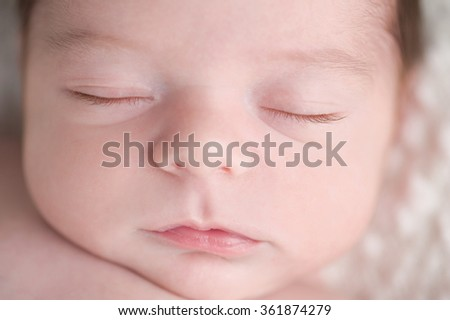 An overhead, close-up shot of a sleeping, three week old, newborn baby boy's face.  - stock photo