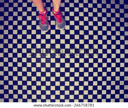 an overhead photo of a pair of tennis shoes on a grungy dirty checkered tile floor toned with a retro vintage instagram filter app or action - stock photo