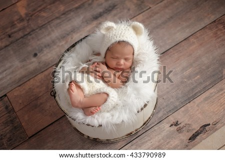 An overhead shot of an eleven day old newborn baby girl sleeping in a wooden bucket. She is wearing a crocheted, white bear bonnet. Shot in the studio on a rustic wood background.