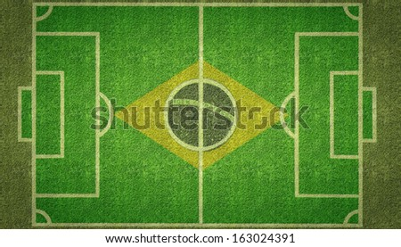 An overhead view of a football soccer pitch with white markings and the flag of Brazil painted on grass. - stock photo