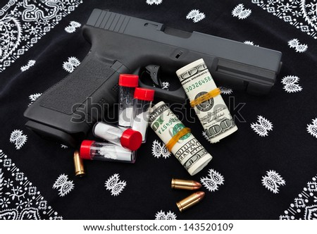 An overhead view of a pistol, ammo, drugs, and money resting on a black bandana. - stock photo