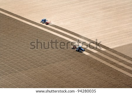 An overhead view of farmland being plowed and planted. - stock photo