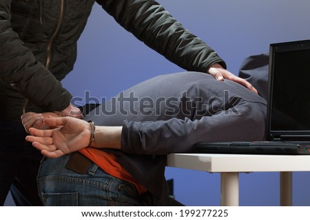 An overpowered hacker being arrested by the police - stock photo
