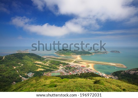 An overview of a seaside town with some white clouds in the sky. - stock photo