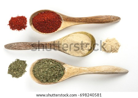 An overview of wooden spoons filled with red pepper powder, garlic powder, and basil leaves.
