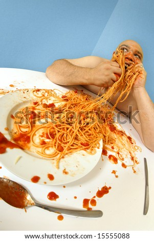 An overweight man enjoying a plate of spaghetti.  Shot with fish-eye lens.  Focus is on the face.