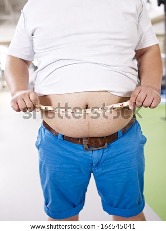an overweight young man measures his belly. - stock photo