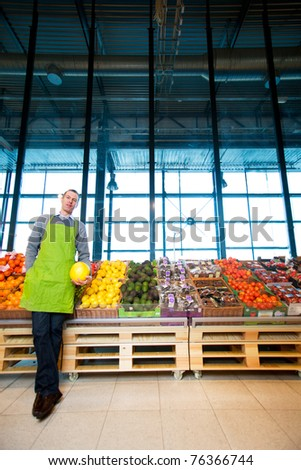 An owner of a grocery store standing by fruits and vegetables - stock photo