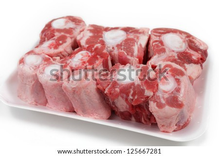 An oxtail, cut into segments and presented on a supermarket-style polystyrene tray - stock photo