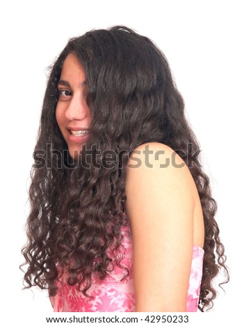 An portrait of a young teenager from the side and her long curly hair hangs down, in a pink dress. On white background. - stock photo