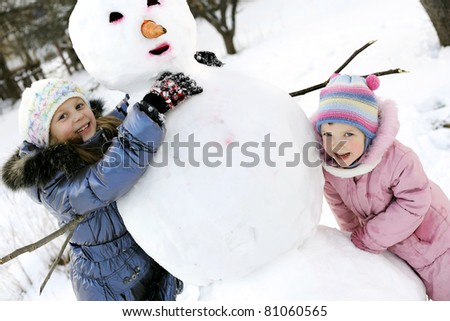 An portraits of happy sisters posing with snowman - stock photo