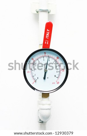 An pressure meter build on white wall. - stock photo