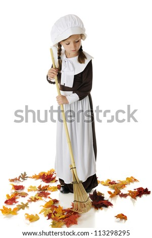 An pretty elementary Pilgrim girl raking colorful autumn leaves.  On a white background. - stock photo