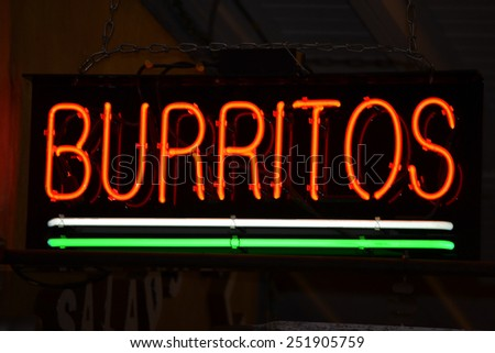An red neon sign that reads Burritos