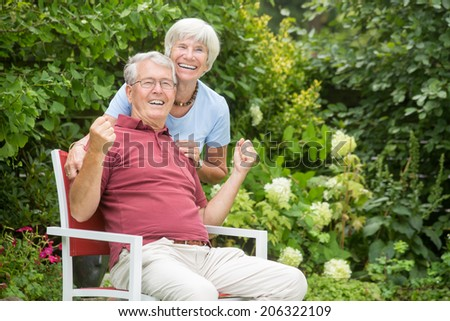 An romantic elderly couple sitting outside and having fun together in a garden - stock photo