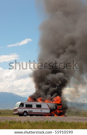 An RV is engulfed in flames at the side of a highway on a hot summer's day.  So much for the vacation...