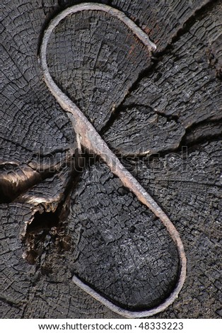 "An ""S' shaped piece of metal embedded into an old wooden beam - stock photo"