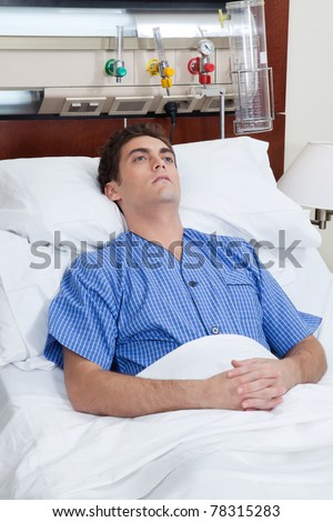An severe male patient at hospital bed - stock photo