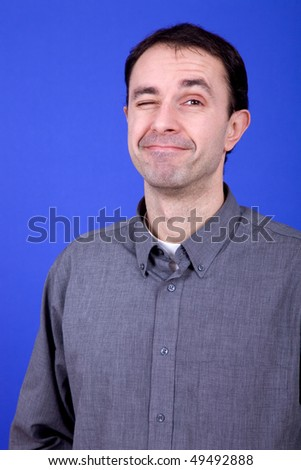 an silly young man portrait over a blue background - stock photo