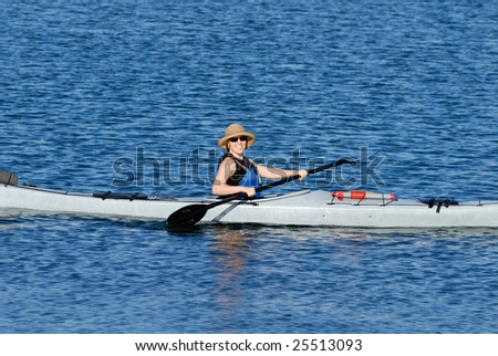 An smiling attractive young woman kayaking in Mission Bay, San Diego, California