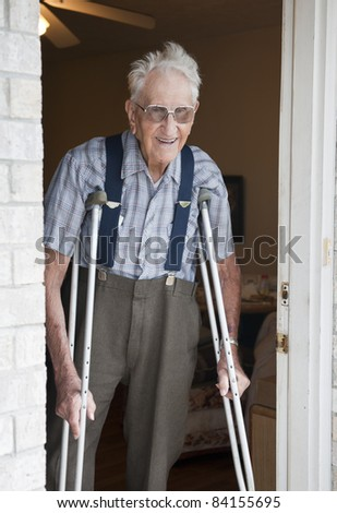 An smiling elderly man standing in the door of his apartment with crutches