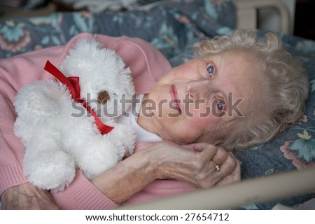 An smiling elderly woman lies down to enjoy a rest at her nursing home care center on a sunny day holding a bear.