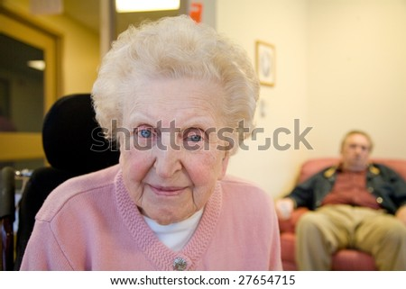 An smiling elderly woman sits down  at her nursing home care center with a man out-of-focus in the background.