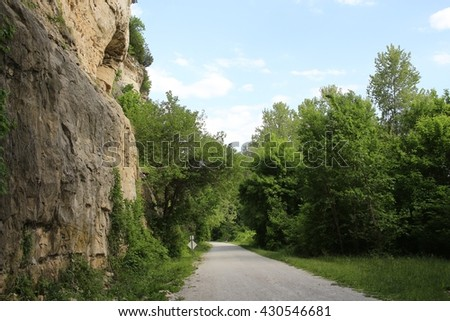 an standing on the edge of a sandstone bluff looking down. - stock photo