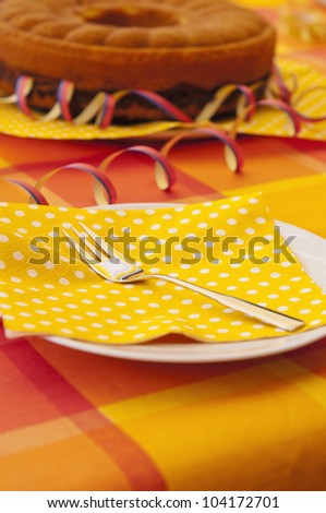 An summer party table setting with fork, napkin and dish. - stock photo
