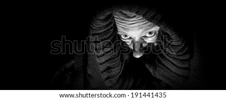 An ugly, scary looking woman in a black shroud; looks like she is  in despair; very shadowy harsh image; black and white panoramic format