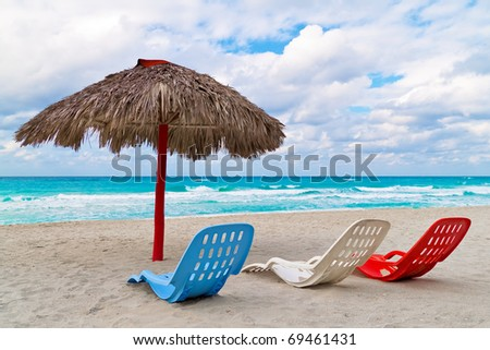 An umbrella and three colorful plastic beds in the sand on a beautiful tropical beach - stock photo