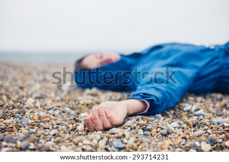 An unconscious woman is lying on a shingle beach - stock photo
