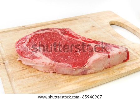 An uncooked rib eye steak on a chopping board - stock photo