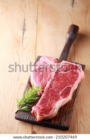 An uncooked tender lean porterhouse steak with a sprig of fresh aromatic rosemary for seasoning on an old rustic wooden board on a wood table with copyspace, view from above - stock photo